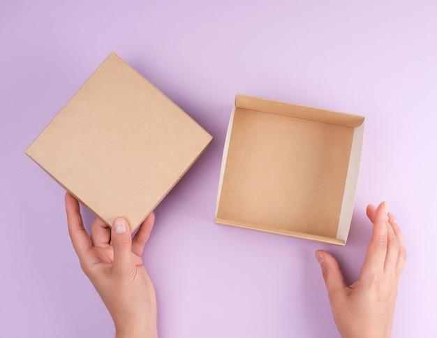 La ragazza apre una scatola quadrata marrone su uno sfondo viola Foto Premium