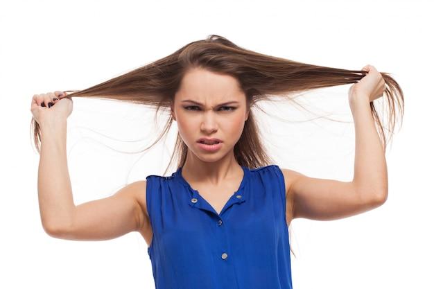 La ragazza arrabbiata tiene i capelli tra le mani Foto Gratuite