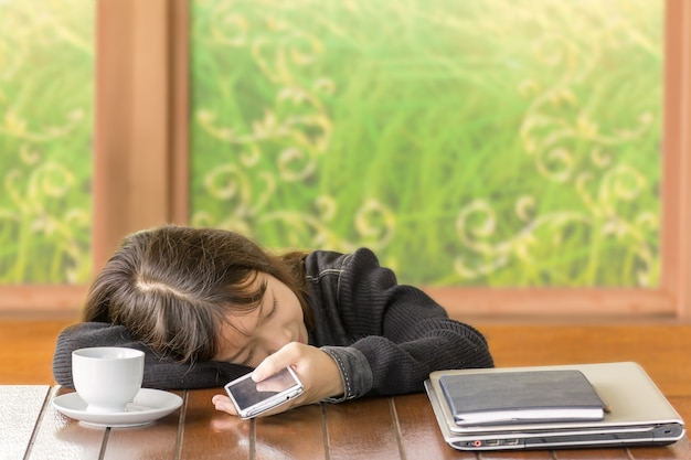 La ragazza asiatica che dorme e tiene lo smartphone a disposizione Foto Premium