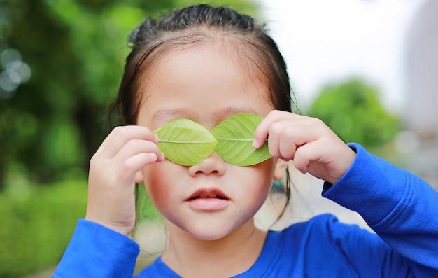 La ragazza asiatica del bambino che tiene una foglia verde che chiude osserva nel fondo verde del giardino. Foto Premium