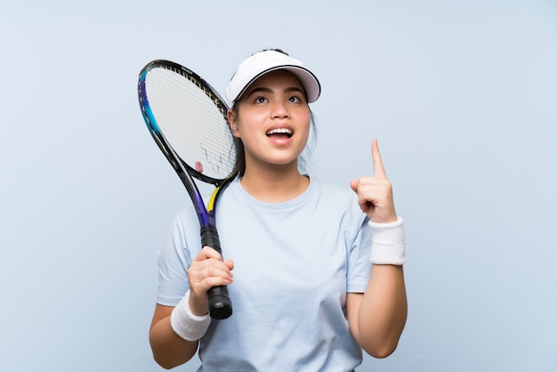 La ragazza asiatica del giovane adolescente che gioca a tennis che intende realizzare la soluzione mentre solleva un dito su Foto Premium