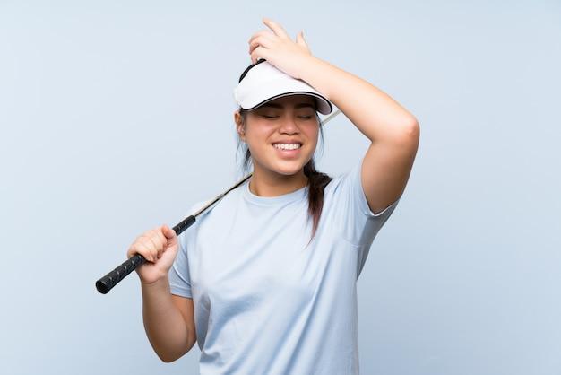 La ragazza asiatica del giovane giocatore di golf sopra fondo blu isolato ha realizzato qualcosa e intendendo la soluzione Foto Premium