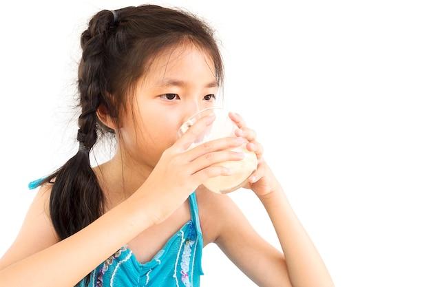 La ragazza asiatica sta bevendo un bicchiere di latte sopra fondo bianco Foto Gratuite