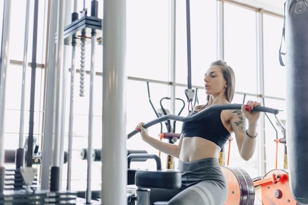 La ragazza atletica attraente si allena le spalle in simulatore. vista dei muscoli della schiena. uno stile di vita sano. Foto Gratuite