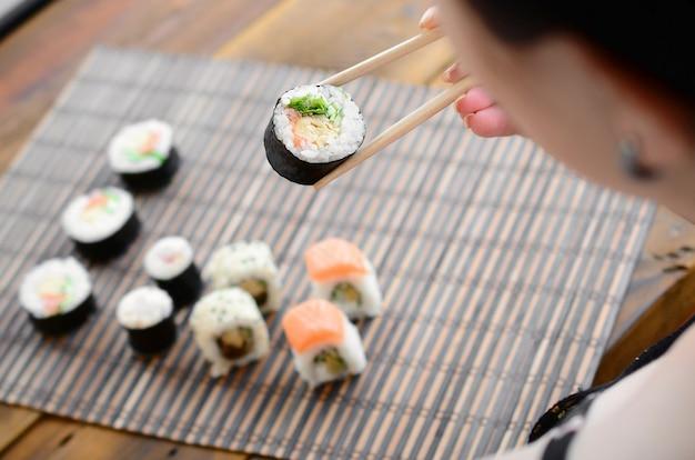 La ragazza castana con le bacchette tiene un rotolo di sushi su un fondo della stuoia di serwing della paglia di bambù. Foto Premium
