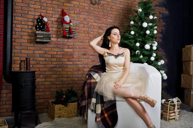 La ragazza castana in vestito ha posato vicino all'albero del nuovo anno con la decorazione di natale nella stanza dello studio del mattone. Foto Premium