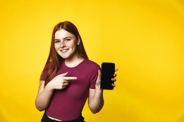 La ragazza caucasica di redhead sorrisa giovane sta tenendo uno smartphone Foto Gratuite