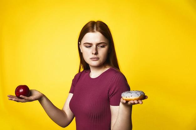 La ragazza caucasica premurosa della testarossa sta tenendo la mela in una mano e la ciambella in un'altra Foto Gratuite