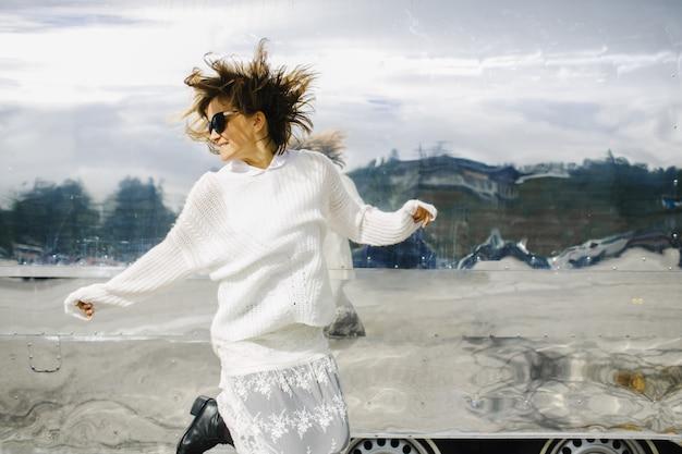 La ragazza che indossa abiti bianchi salta accanto al veicolo luccicante Foto Gratuite