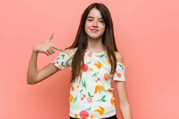 La ragazza che indossa un'estate copre contro una persona della parete che indica a mano una copia della camicia, fiera e sicura Foto Premium