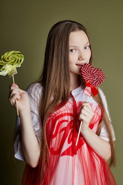 La ragazza che mangia la caramella rotonda lecca la lecca-lecca Foto Premium