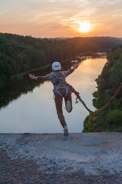 La ragazza che salta dal ponte. una donna con un tempo incredibile è impegnata nel freestyle nel bungee jumping. una giovane donna esegue un trucco inverso nel bungee jumping. salta al tramonto estremamente giovane. Foto Premium