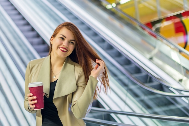 La ragazza che sorride e che tiene tazza di caffè Foto Premium