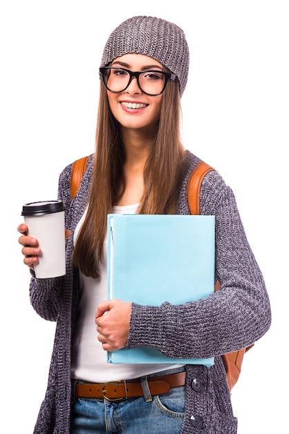 La ragazza con il caffè in mano guarda la parte anteriore. Foto Premium