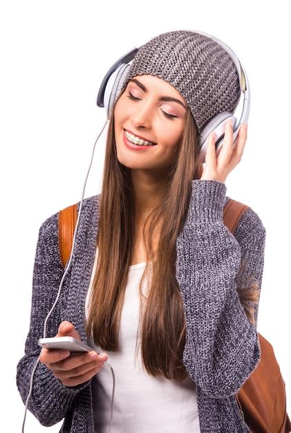 La ragazza con il cappello sorride e ascolta la musica. Foto Premium