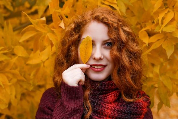 La ragazza dai capelli rossi sveglia con un albero di autunno con una foglia in sua mano sorride e fa smorfie Foto Premium