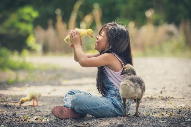 La ragazza dei bambini dell'asia tiene un'anatra in mani Foto Premium