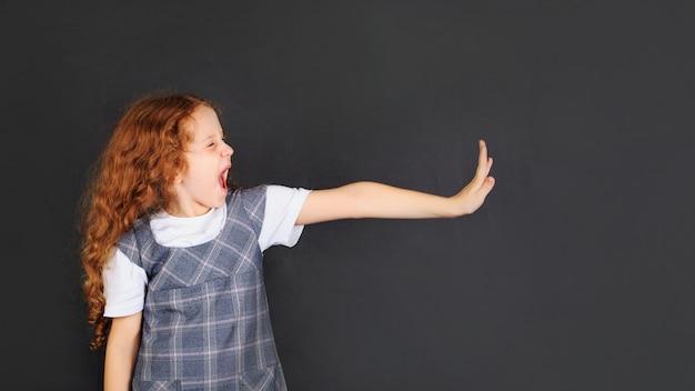 La ragazza della scuola che mostra l'espressione facciale di emozione disgustata e la mano si alzano per fermarsi o proteggere Foto Premium