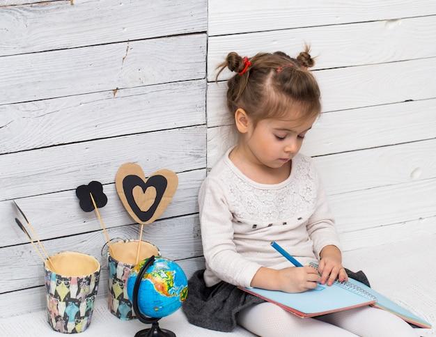 La ragazza della scuola si siede su un bianco in legno con un globo in mano e un quaderno Foto Gratuite