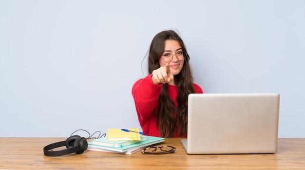 La ragazza dello studente dell'adolescente che studia in una tabella indica il dito con un'espressione sicura Foto Premium