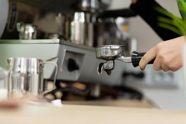 La ragazza di barista sta preparando il caffè aromatico con una macchina da caffè Foto Premium