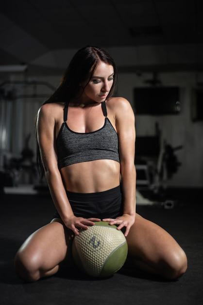 La ragazza di forma fisica posa con una palla in palestra Foto Premium
