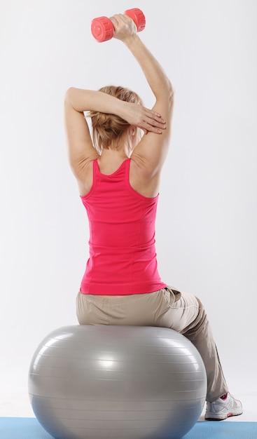 La ragazza di forma fisica si prepara in palestra sulla palla di forma fisica Foto Gratuite