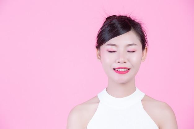 La ragazza di modo si agghinda con i gesti di mano su un fondo rosa. Foto Gratuite