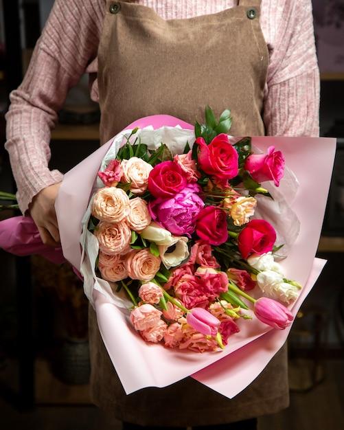 La ragazza di vista frontale tiene il bello mazzo delle rose variopinte tulipani e peonie in un involucro di carta Foto Gratuite