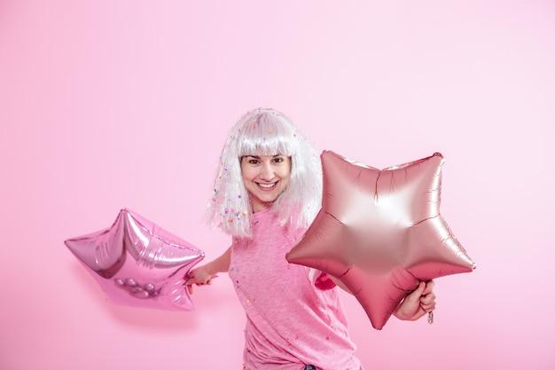 La ragazza divertente con capelli d'argento dà un sorriso ed emozione su fondo rosa. giovane donna o ragazza teenager con palloncini e coriandoli Foto Gratuite