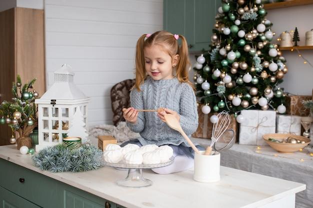 La ragazza divertente sveglia sta sedendosi sul tavolo da cucina a casa di natale Foto Premium