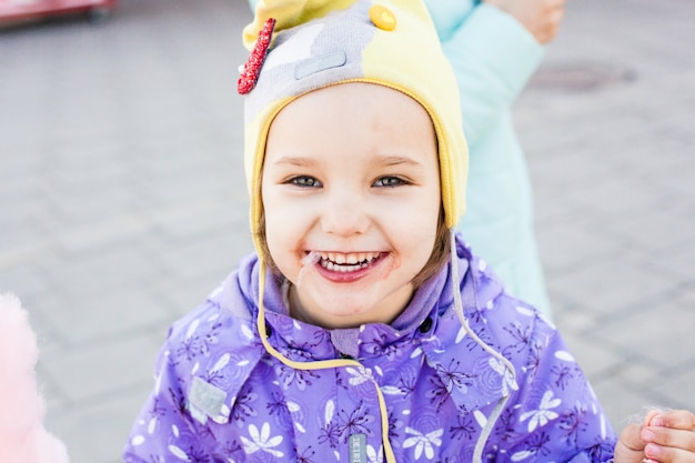 La ragazza è dolce, zucchero filato, gioia, cammina con la famiglia Foto Premium