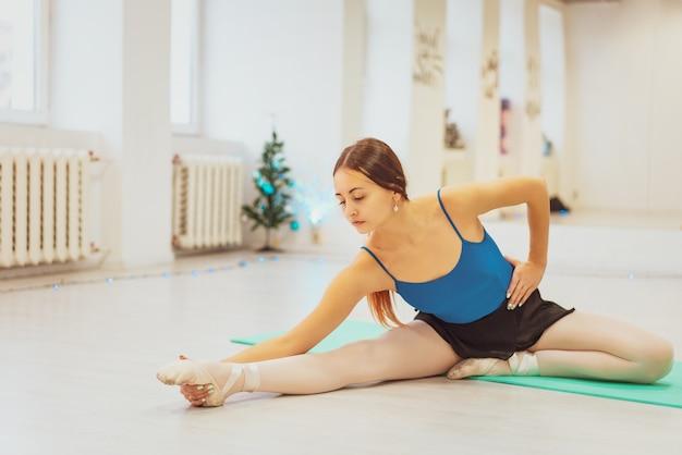 La ragazza è impegnata in ginnastica, facendo stretching in palestra Foto Premium