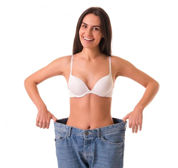 La ragazza esile sta tirando i suoi jeans e sta mostrando la perdita di peso. Foto Premium