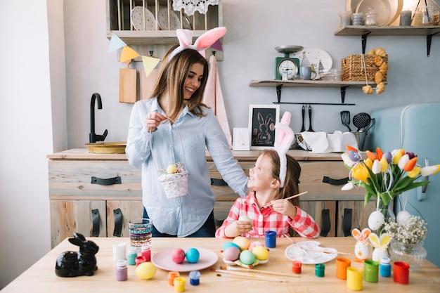 La ragazza felice che dipinge le uova per pasqua vicino alla madre con il canestro Foto Gratuite