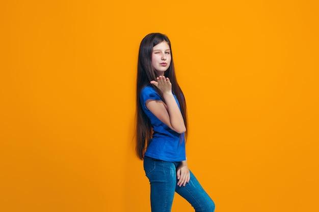 La ragazza felice che sta e che sorride contro la parete arancio Foto Gratuite