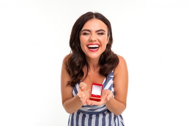 La ragazza felice con capelli castani in un vestito con una scollatura dà una scatola con un anello di fidanzamento in mani su un bianco Foto Premium
