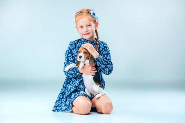 La ragazza felice e un cucciolo di beagle su sfondo grigio Foto Gratuite