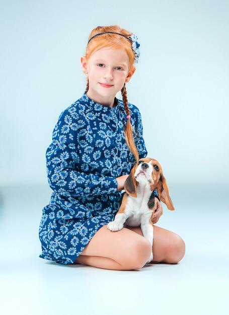 La ragazza felice e un cucciolo di beagle sulla parete grigia Foto Gratuite