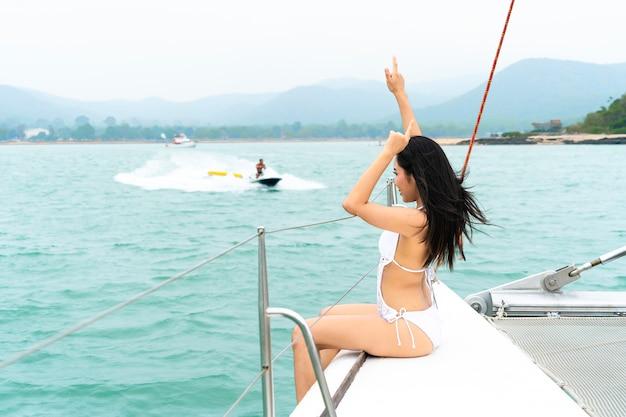 La ragazza felice sexy del bikini si siede sull'yacht della barca con davanti al mare ed al cielo Foto Premium