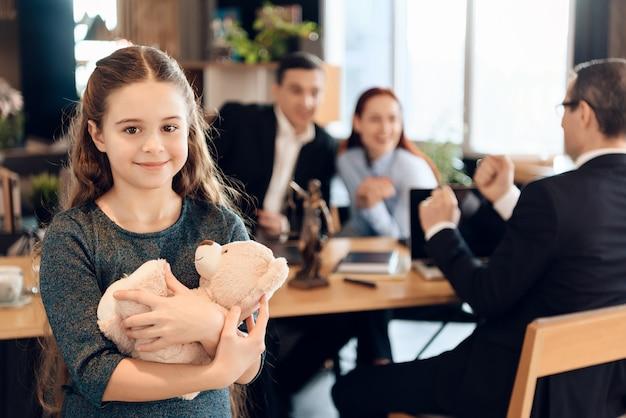 La ragazza felice sta abbracciando l'orsacchiotto all'ufficio dell'avvocato di famiglia. Foto Premium