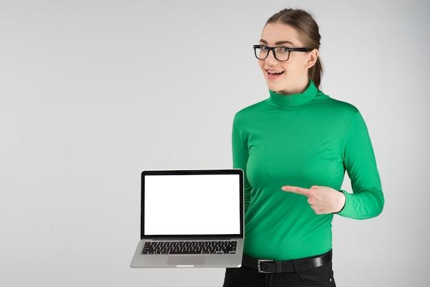 La ragazza felice tiene un computer portatile e che indica uno schermo. -- immagine Foto Premium