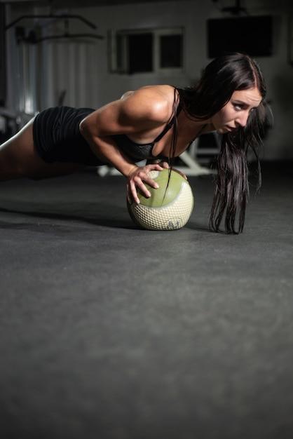 La ragazza fitness fa flessioni sulla palla Foto Premium