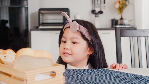 La ragazza giapponese asiatica mangia il pane a casa. le donne asiatiche si sentono felici pick sandwich che lo ha messo sul tavolo sul tavolo in cucina moderna a casa la mattina. Foto Gratuite