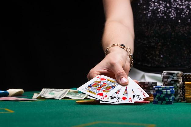La ragazza gioca a poker in un casinò con patatine, dollari e vino Foto Premium