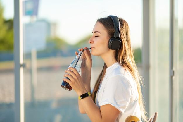 La ragazza gode di bere soda nella musica d'ascolto Foto Premium