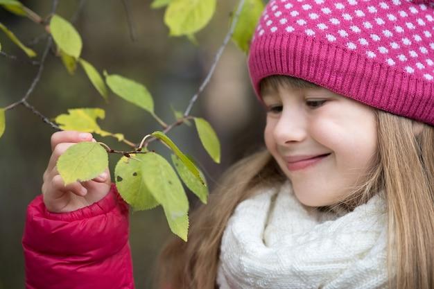 La ragazza graziosa del bambino che indossa l'inverno caldo copre la tenuta del ramo di albero con le foglie verdi nella stagione fredda all'aperto. Foto Premium