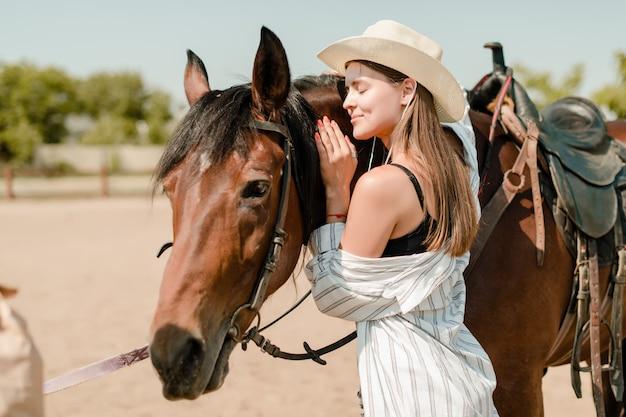 La ragazza graziosa in un'azienda agricola abbraccia il suo cavallo Foto Premium