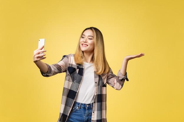 La ragazza graziosa prende un autoritratto con il suo smartphone. selfie ragazza asiatica Foto Premium