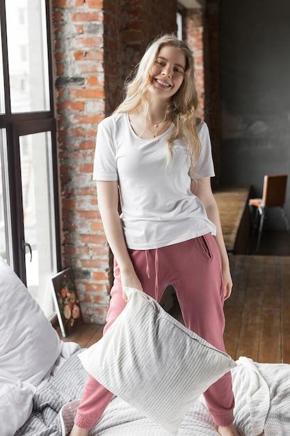 La ragazza graziosa si è vestita in pantaloni del pigiama rosa e maglietta bianca che stanno su un letto con un cuscino vicino ad una finestra in appartamento del sottotetto Foto Premium